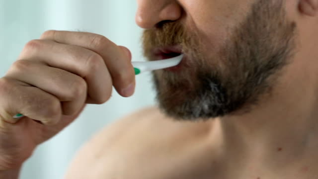 bearded man feels tooth pain while cleaning teeth, showing toothbrush with blood - denti video stock e b–roll