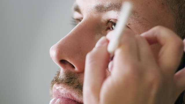 stockvideo's en b-roll-footage met bebaarde mens die make-up krijgt - vetschmink