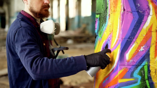 skäggig man graffiti målare använder aerosol färg för att dekorera pelaren i gammal industribyggnad. modern urban konst, kreativa ungdomar och hobby konceptet. - väggmålning bildbanksvideor och videomaterial från bakom kulisserna
