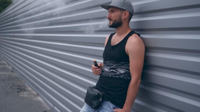 sakallı adam rahat kıyafetler vaping ve elektronik sigara buhar puffs kapalı icar - nikotin stok videoları ve detay görüntü çekimi
