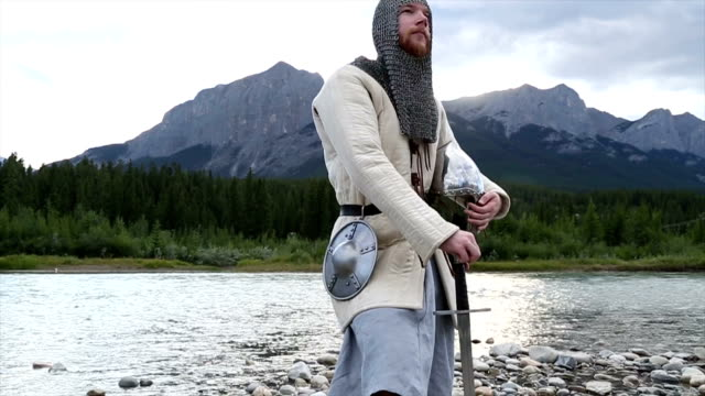 Bearded man in medieval/viking costume pauses by river video