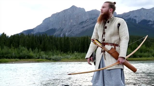 vídeos y material grabado en eventos de stock de hombre barbudo en traje medieval/viking hace una pausa por río - vikingo