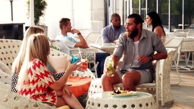 Bearded man in shorts talking with friends in lobby video