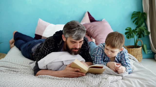 Bearded man is reading book to his little son lying on bed in nice cozy bedroom. United family, spending leisure time and raising children concept. video