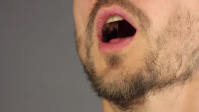 bearded man opens his mouth, sneezes, wipes nose with his hand, side view, closeup macro - рот стоковые видео и кадры b-roll
