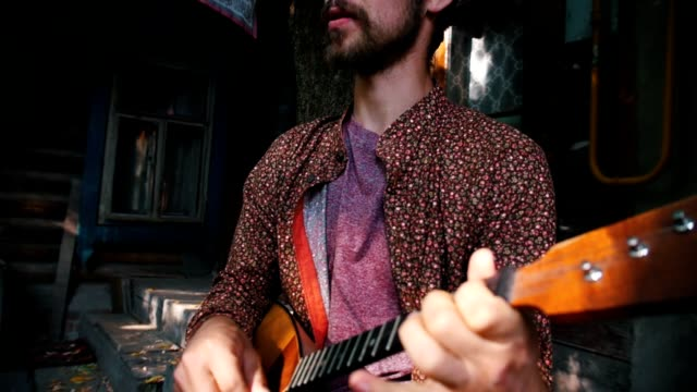 a bearded man playing balalaika outdoors - славянская культура стоковые видео и кадры b-roll