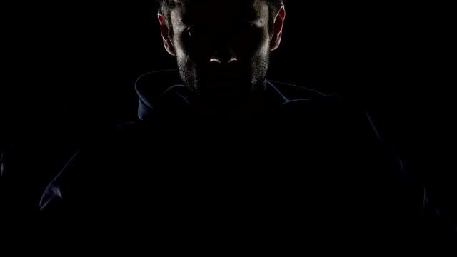 vídeos de stock e filmes b-roll de bearded man putting on hood, hiding from people, anonymous dark silhouette - capuz