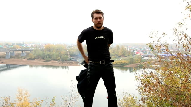 Bearded man removes black leather jackets and throws it video