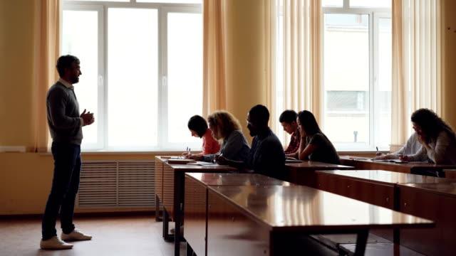 l'insegnante universitario barbuto sta leggendo lezioni a studenti adulti e gesticolando , i giovani lo scrivono e lo ascoltano. istruzione superiore e concetto di gioventù. - esame università video stock e b–roll