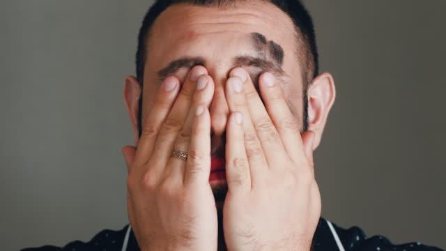 stockvideo's en b-roll-footage met bebaarde mens veegt cosmetica van zijn gezicht - vetschmink