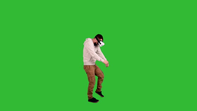bearded man with glasses of virtual reality frightened and fighting off something on a green background video