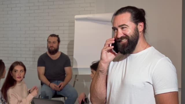 Hombre de negocios maduro barbudo hablando en el teléfono con alegría - vídeo