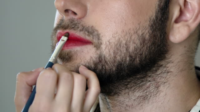Bearded metrosexual man gettinng makeup Closeup of handsome bearded metrosexual man getting makeup. Unrecognizable makeup artist paints lips ща handsome bearded man in a red color close-up. The hand paints with a brush in the bright red color of the lips transgender stock videos & royalty-free footage