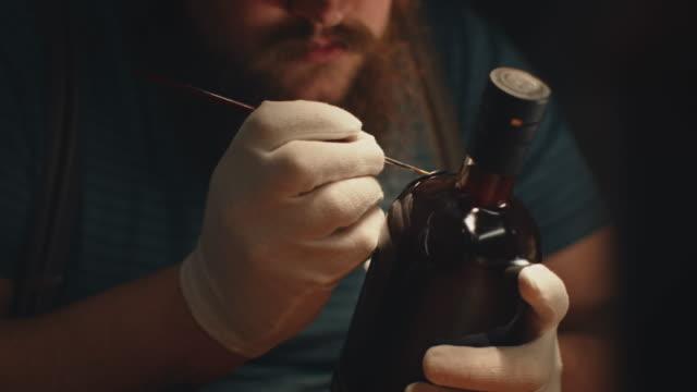 Bearded owner painting seal on bottle