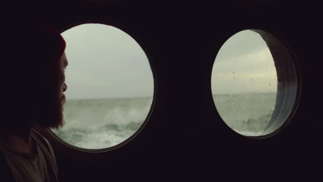 Bearded sailor at the porthole window of a vessel in a rough sea video