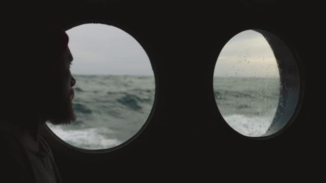 bearded sailor at the porthole window of a vessel in a rough sea - uomo nostalgia video stock e b–roll