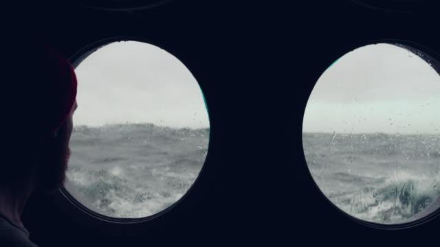 skäggiga sjöman vid hyttventil fönster av ett fartyg i en grov sjö - film tagen utanför usa bildbanksvideor och videomaterial från bakom kulisserna