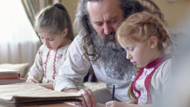 bearded senior man helping kids with homework - славянская культура стоковые видео и кадры b-roll