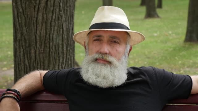 skäggig senior man på en bänk i staden - endast en medelålders man bildbanksvideor och videomaterial från bakom kulisserna