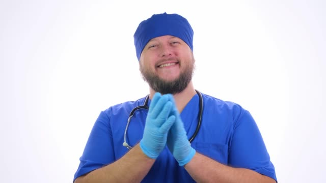 Bearded smiling male medical worker in blue clothes claps his hands