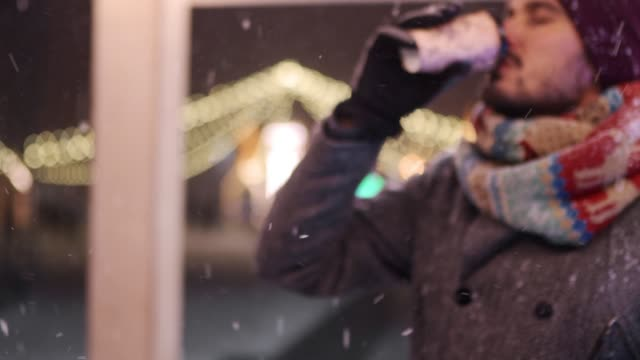 Bearded stylish man in gray coat and knitted scarf drinks coffee out of paper cup and looks to the camera smiling. Christmas market and New Year winter fair on background. Snowy night. Winter fashion