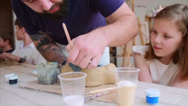 Bearded teacher in shows his pupil girl how to color her handmade toy from clay.
