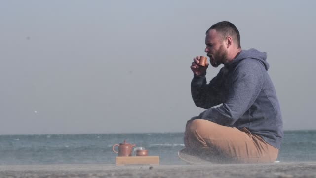 Bearded White Man Drinks Chinese Tea on a Pier by the Sea. The Wind Sweeps Sand and Seagulls Fly in the Background video