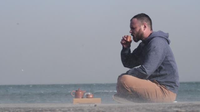 Homem branco barbudo bebe chá chinês em um píer à beira-mar. O vento varre areia e gaivotas voam ao fundo - vídeo