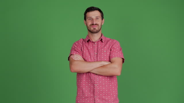 bearded young adult man looks at camera, smiling, arms crossed on a green background - stare in piedi video stock e b–roll