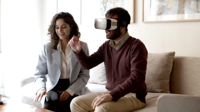 Bearded young man gesturing while using VR headset at home