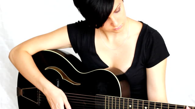 Beatiful girl playing acoustic guitar. video