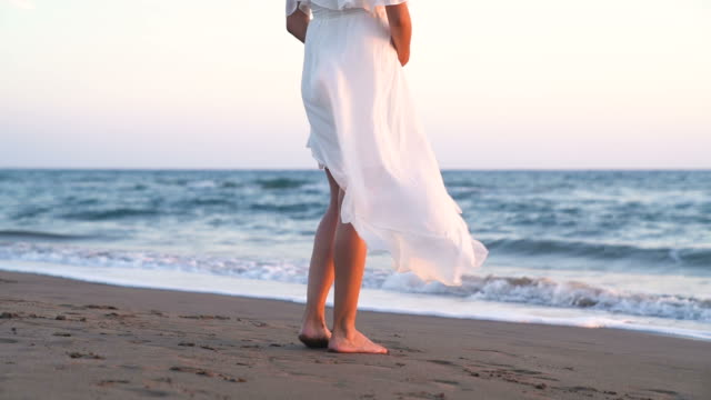 Beatiful Pregnant Woman with White Dress on the Beach