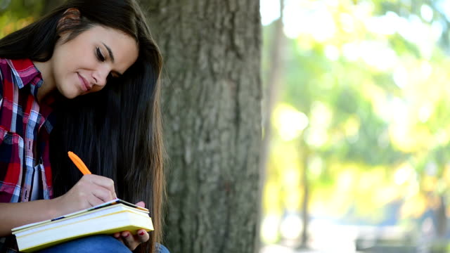Beatiful Teenage Girl Studying in the Park, close-up video