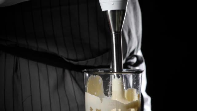 vidéos et rushes de passage à tabac de mayonnaise maison avec de l'huile d'olive. mélanger les ingrédients de la sauce. le chef utilise un mélangeur - batteur électrique