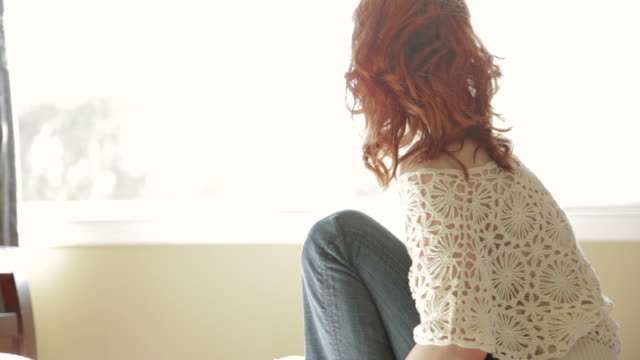 Beautful redhead woman backlit by sun looking out window  dyed red hair stock videos & royalty-free footage