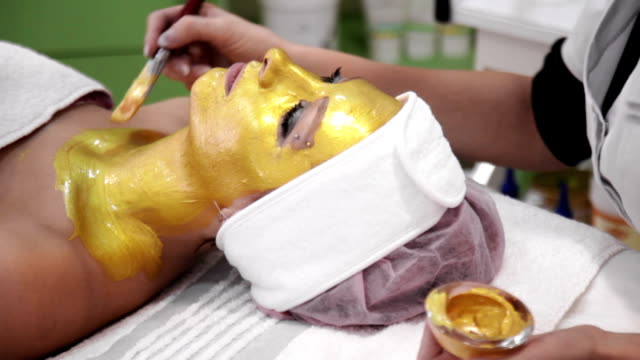 beautician applies cosmetology mudpack on client's neck - face mask stock videos & royalty-free footage