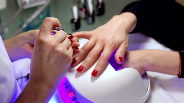 a beautician applies red nail polish to a young womans nails. - nail work tool stock videos & royalty-free footage