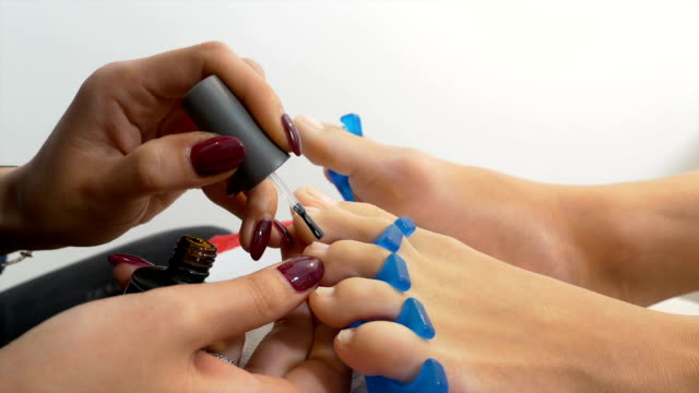 Beautician applies treatment on toe nails of client video