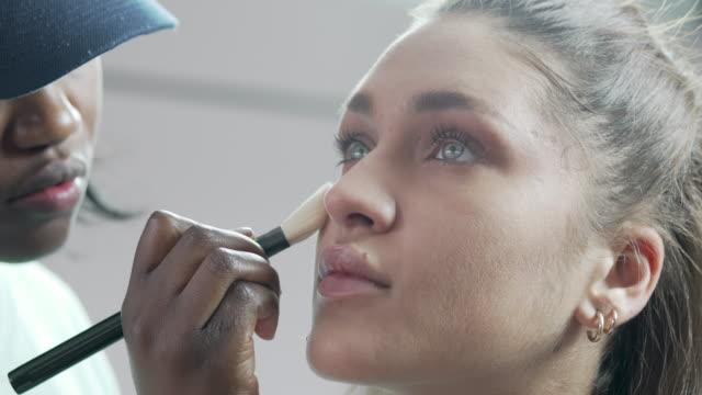 en kosmetolog tillämpa rouge till en modell ansikte - makeup artist bildbanksvideor och videomaterial från bakom kulisserna