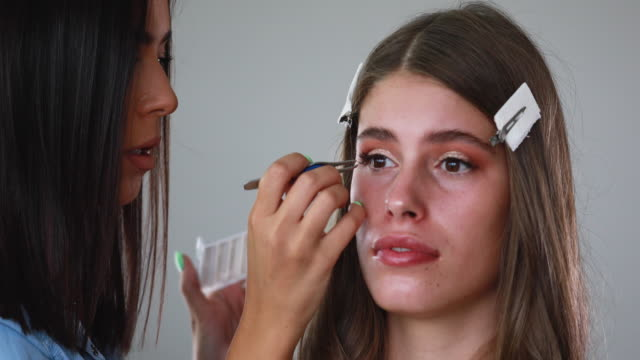 Beautician applying false eyelash to a beautiful young woman