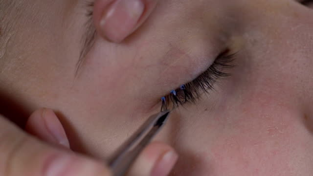 目尻、グラマーで化粧品の接着剤でつけまつげを適用する美容師 - まつげ点の映像素材/bロール