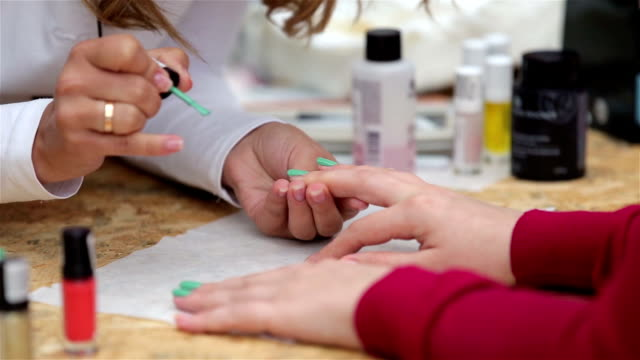 Beautician color nail polish to the client in the beauty salon. Close-up. video