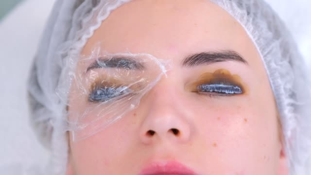 Beautician covered woman lashes file, pads and towel, lift eyelashes procedure. video