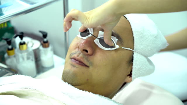 4k beautician doctor wearing light protective eyepatch safety glasses goggles ipl to handsome man patient eye at beauty salon - depilacja filmów i materiałów b-roll