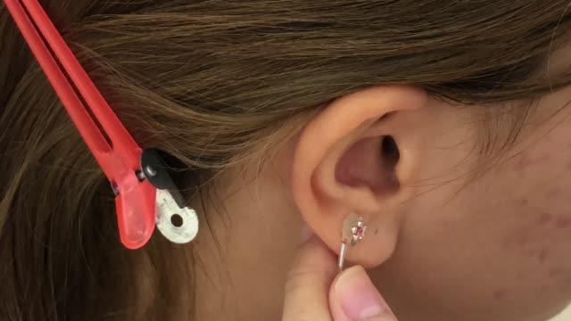 Beautician doing ear piercing procedure in beauty salon