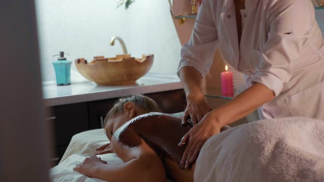 Beautician doing massage with chocolate to young beautiful woman at spa salon video