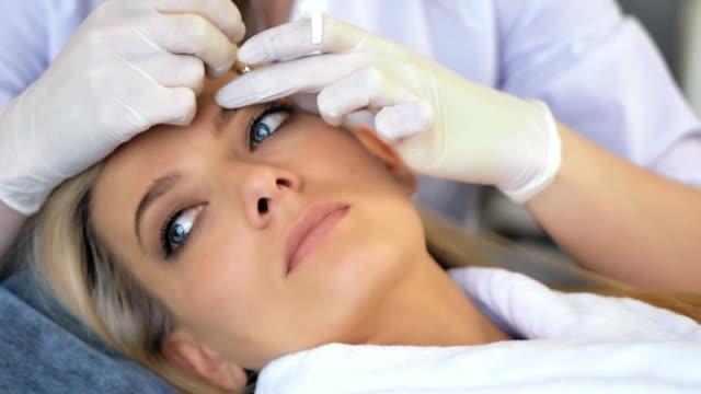 vídeos de stock e filmes b-roll de beautician doing permanent makeup for eyebrows in beauty salon - sobrancelha