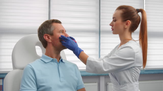 Beautician drawing correction lines on male patient's face