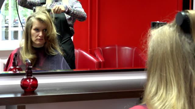 vidéos et rushes de esthéticienne, sécher les cheveux de la fille après la nouvelle coupe de cheveux au salon. fullhd - salons et coiffeurs