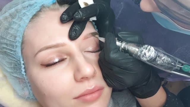 vídeos de stock e filmes b-roll de beautician female applies permanent makeup on eyebrows, tattoo eyebrows on beautiful models in a beauty parlor - sobrancelha